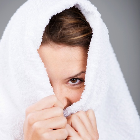 shyness: Young cheerful female covering her head with towel