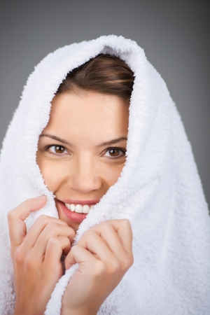 Smiling woman covering her head with towel photo