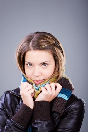 Pretty woman covering her neck with a scarf over the grey background Stock Photo - 21110866