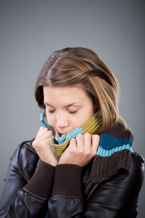 Woman freezing with scarf and jacket isolated on Stock Photo - 21110867