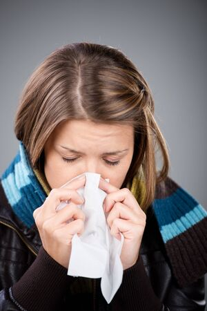 warming therapy: Sneezing woman wearing jacket and scarf in a close up shot