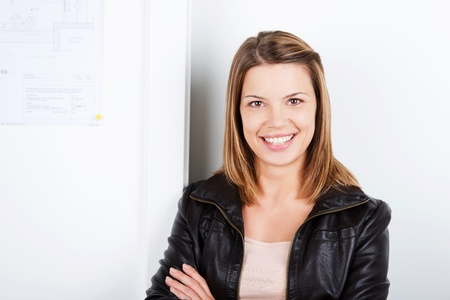 Portrait of smiling brunette woman leaning on the wall photo