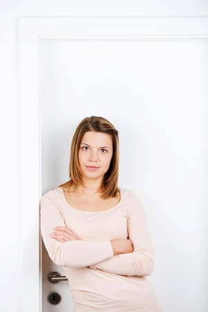 Young beautiful female posing with arms crossed over the white background photo