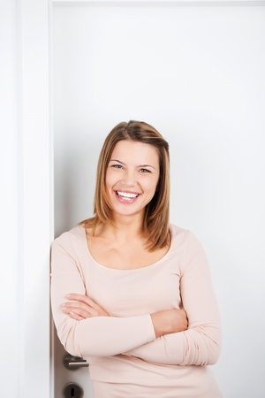 standing against: Portrait of happy brunette female leaning on a door frame