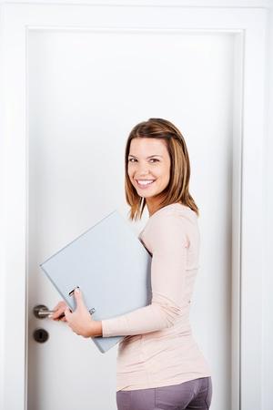 abriendo puerta: Mujer feliz con la computadora portátil mientras se abre la puerta