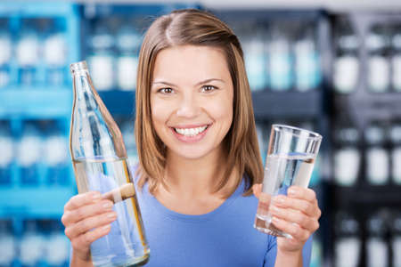 Smiling woman holding water bottle and glass in a close up shot Stock Photo - 21111063