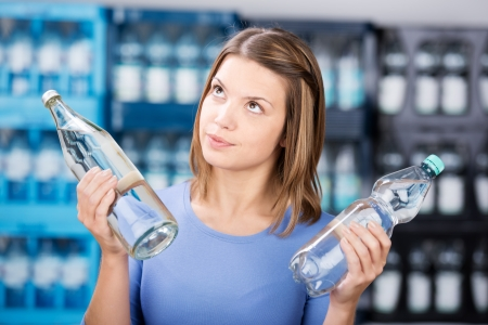 Looking up woman holding two glass bottle with water Stock Photo