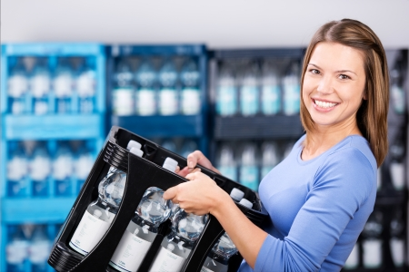 beverage: Smiling woman holding a box of refundable bottles