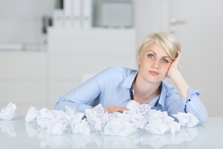 writers block: Young thoughtful female executive sitting with crumpled paper balls at desk looking in camera