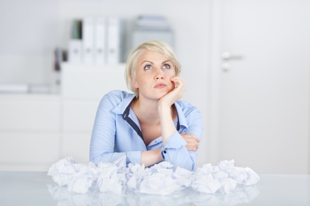 seeking an answer: Young thoughtful female executive sitting with crumpled paper balls at desk looking up