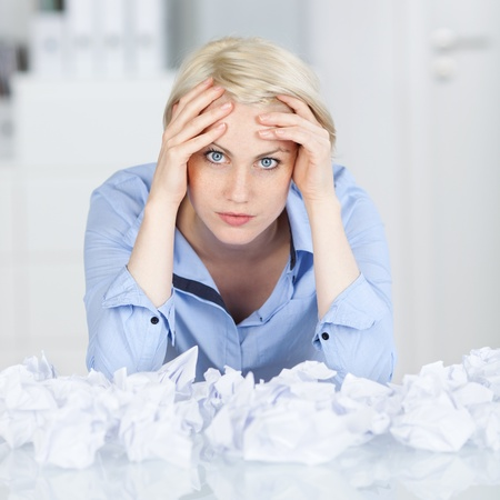 writer: Portrait of a tired young female executive sitting with crumpled paper balls at desk