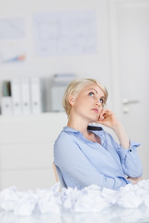 writers block: Blond businesswoman with hand on chin looking for new ideas in the office