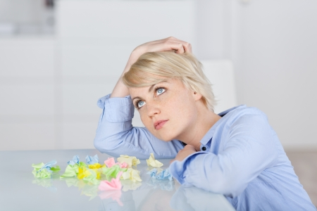 Young thoughtful female executive sitting with colorful crumpled paper balls at desk photo