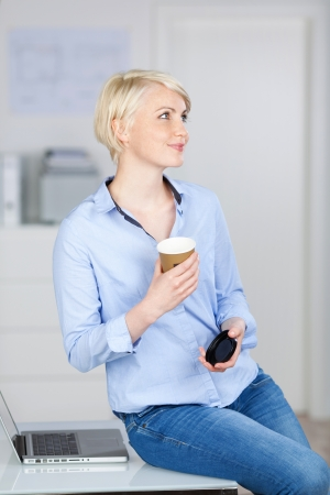 Portrait of a young smiling businesswoman with coffee cup looking up at office desk photo