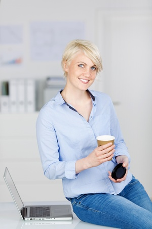 Portrait of a young smiling businesswoman with disposable coffee cup by laptop at office desk Stock Photo - 21111122
