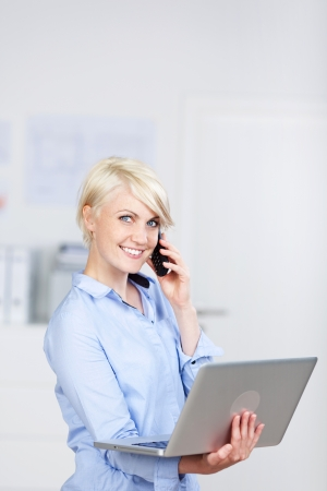 Portrait of a young smiling businesswoman using laptop and cellphone photo
