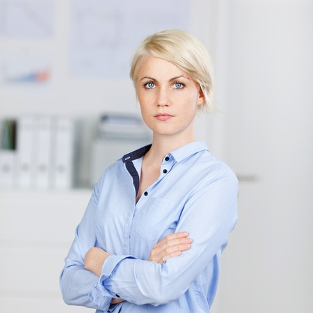 Portrait of a confident and beautiful young businesswoman standing with arms crossed photo