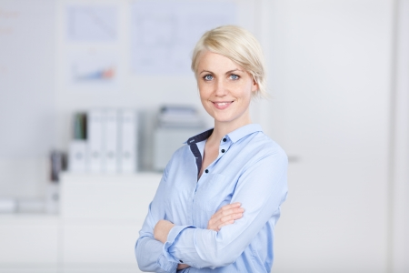 Portrait of a smiling confident and beautiful young businesswoman standing with arms crossed