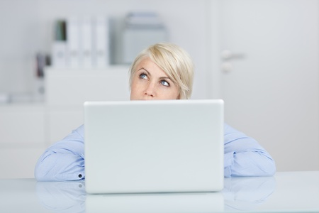 target thinking: Young blond businesswoman looking up thoughtfully in front of a laptop at office desk Stock Photo