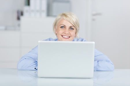 facing: Happy young blond businesswoman looking up in front of a laptop at office desk