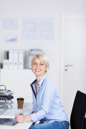 Side view portrait of a young laughing businesswoman sitting at office desk photo