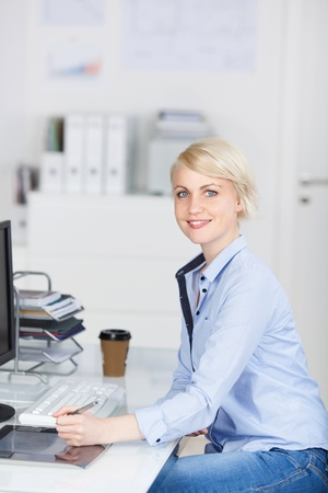 Side view of a young smiling businesswoman sitting at office desk photo