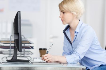 grafik: Seitenansicht einer jungen Frau, Grafik-Designer, der an Computer mit Zeichenblock am Schreibtisch