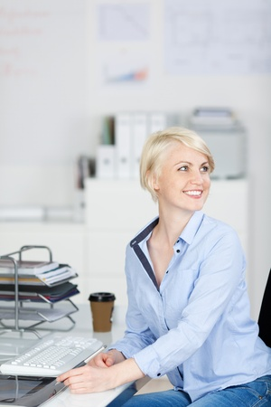 Smiling young businesswoman sitting at office desk and looking away Stock Photo - 21111169