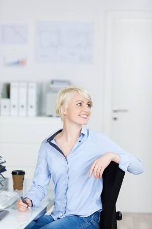 Confident and beautiful young blond businesswoman looking away in office photo