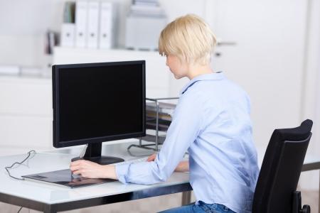 monitor de computadora: Vista de una mujer de negocios joven rubia que usa el ordenador en el escritorio de oficina
