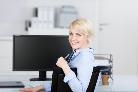 自信を持って、美しい若い実業家のオフィスの机で笑顔の肖像画