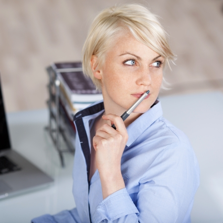 target thinking: Closeup of a beautiful thoughtful female executive with pen looking away at office desk