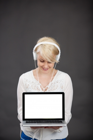 Happy young blond woman with headphones holding laptop against gray background photo