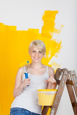 Portrait of a young blond woman with paint roller and bucket by ladder in front of half yellow painted wall photo