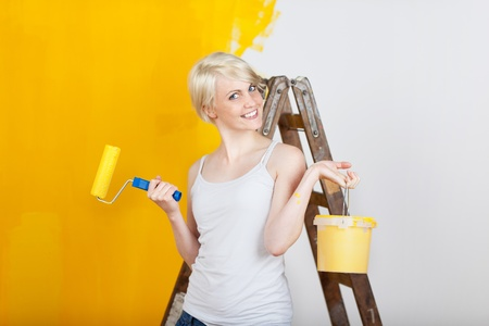 redecorating: happy woman with paint tools painting her apartment yellow