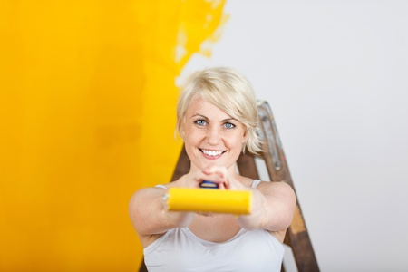 happy woman showing paint roller with yellow color photo