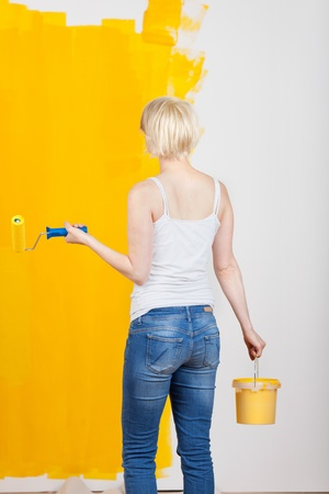 redecorating: Rear view of a young casual woman with paint roller and bucket in front of half yellow painted wall