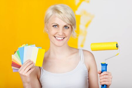 colours tints: Young woman holding out color samples and paint roller against half yellow painted wall