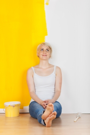 paintings: Full length of a thoughtful young woman sitting in front of a half yellow painted wall