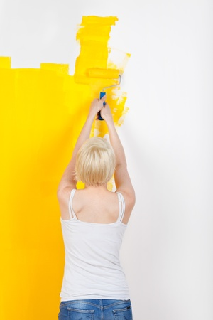 Rear view of a young blond woman painting the wall yellow photo