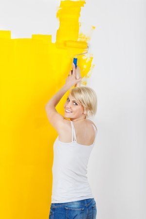 Portrait of a smiling young blond woman painting the wall yellow photo