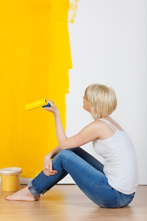 Young casual woman with paint roller sitting on floor and looking at half yellow painted wall photo