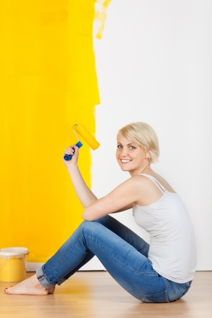 Side view portrait of a young casual woman with paint roller and bucket sitting on floor in new apartment photo