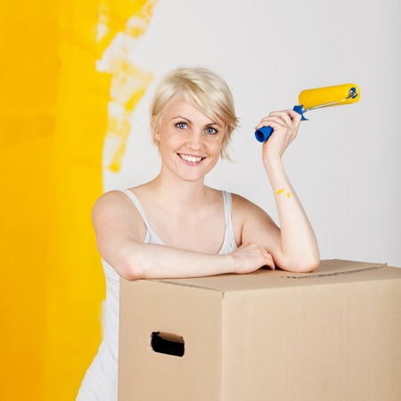 Portrait of a young casual woman with cardboard box and paint roller in front of half yellow painted wall photo