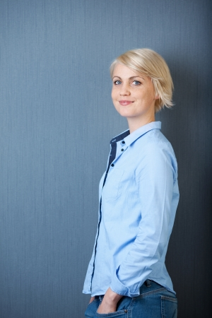 hand in pocket: Portrait of a casual young blond woman standing against blue background