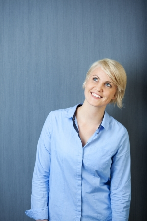 Portrait of a smiling young blond woman standing against blue background looking up photo