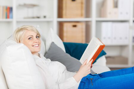 smiling woman relaxing with a book on sofa