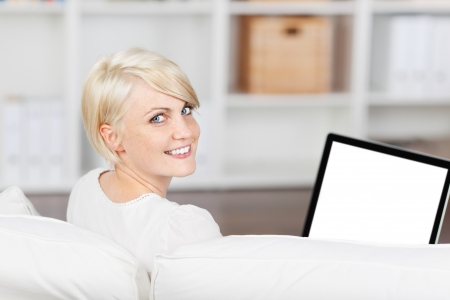 looking at computer screen: Portrait of a beautiful smiling woman with laptop sitting on sofa at home