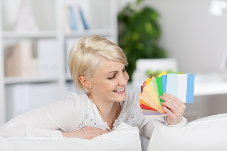 Happy blond young woman holding color samples while sitting on couch at home photo