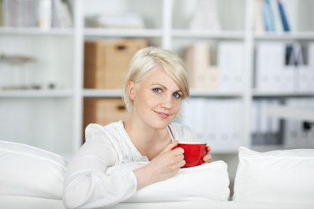 Portrait of a casual young woman with a cup of coffee on sofa at home photo
